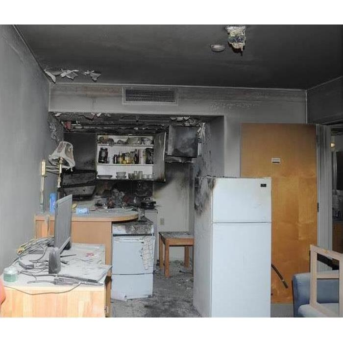 white fridge brown, door, white oven open kitchen cabinet, wall lamp black wall and gray soot from fire coating all