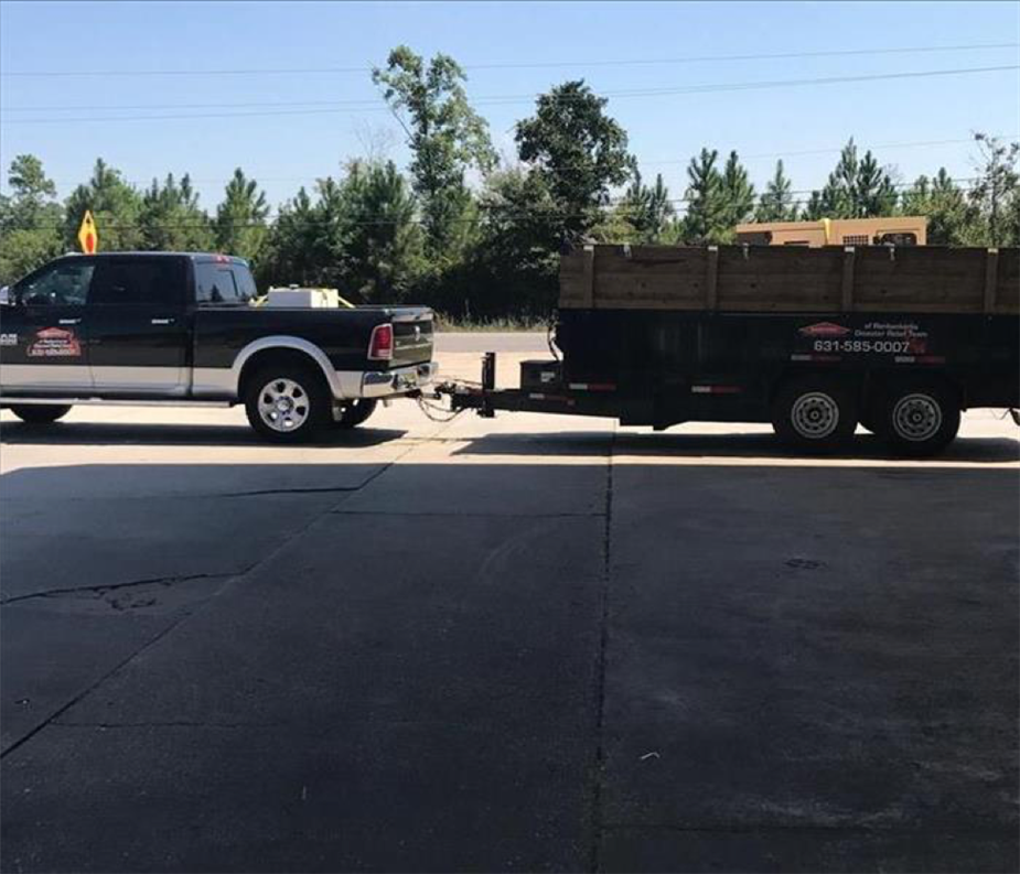 black pick up truck towing a large open garbage trailer